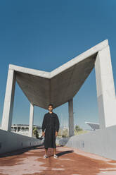 Young man wearing black kaftan standing on a footbridge - AFVF05206