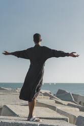 Young man wearing black kaftan on concrete blocks at the coast - AFVF05209