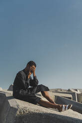 Young man wearing black kaftan sitting on concrete blocks under blue sky covering his face - AFVF05212