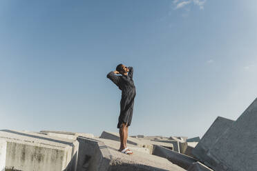 Young man wearing black kaftan standing on concrete blocks under blue sky - AFVF05215
