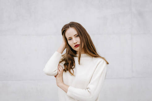 Close portrait of pretty woman with loose hair on white urban background - TCEF00061