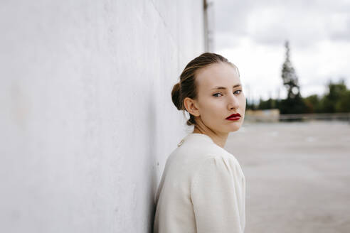 Portrait of serious young woman with red lips leaning against wall - TCEF00064