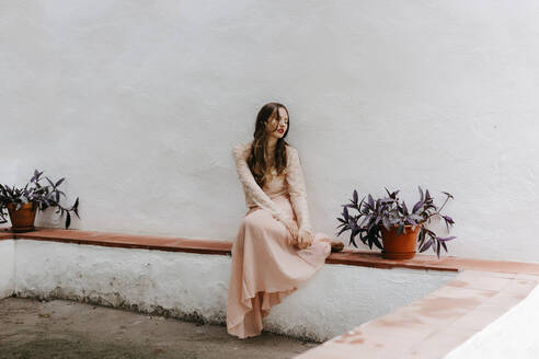 Melancholic woman with romantic look sitting in a white house - TCEF00070