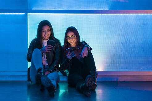 Portrait of two smiling teenage girls sitting in front of blue glass pane looking at smartphones - DLTSF00420