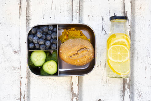 Bottle of lemonade and lunch box with cucumber slices, blueberries and bun with lentil paste - LVF08550