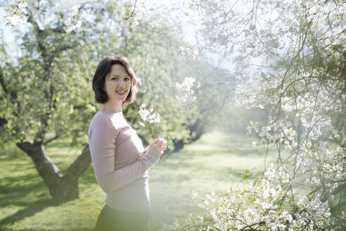 Portrait of smiling woman with twig of blossoming cherry tree at sunlight - EYAF00893