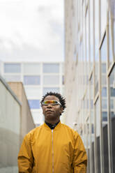 Portrait of mature man wearing mirrored sunglasses and yellow jacket in the city - AFVF05264