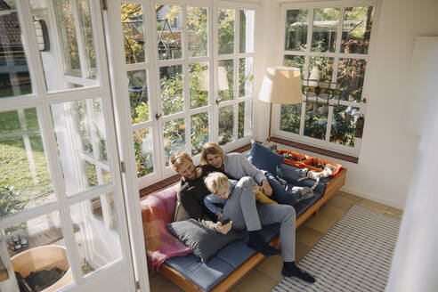 Family using cell phone in sunroom at home - KNSF07005