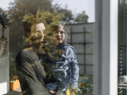 Father carrying son at the window at home - KNSF07020