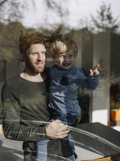 Father and son looking out of window at home - KNSF07023