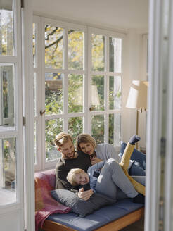 Happy family using cell phone in sunroom at home - KNSF07029