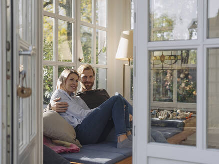Portrait of smiling couple relaxing in sunroom at home - KNSF07035