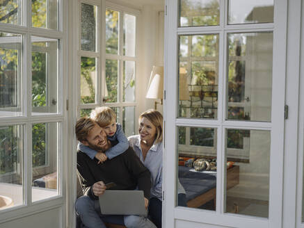Family using laptop and credit card in sunroom at home - KNSF07044