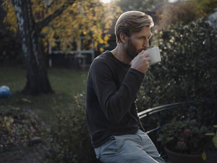 Man having a coffee break in garden - KNSF07062