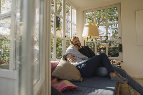 Affectionate couple relaxing in sunroom at home - KNSF07080
