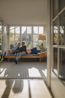 Affectionate couple relaxing in sunroom at home - KNSF07083