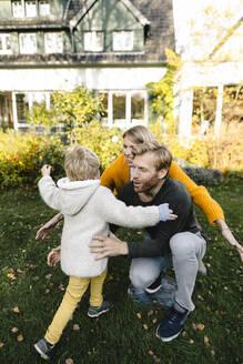 Happy affectionate family in garden - KNSF07098