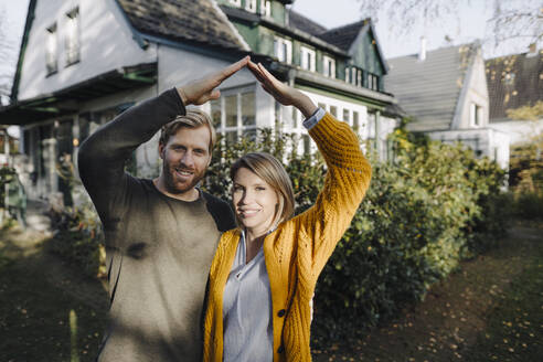 Portrait of smiling couple standing in front of their home - KNSF07101