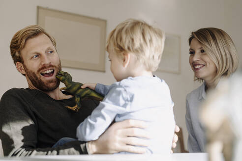 Happy family playing with dinosaur figure at home - KNSF07107