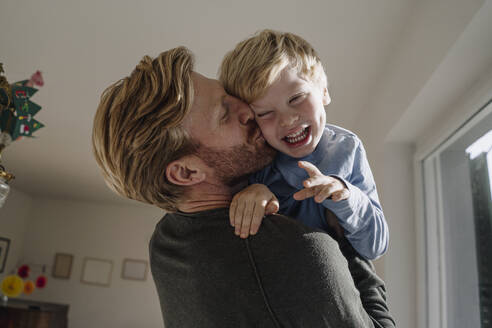 Father carrying and kissing son at home - KNSF07116