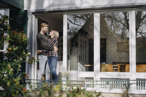 Couple embracing on terrace of their home - KNSF07119
