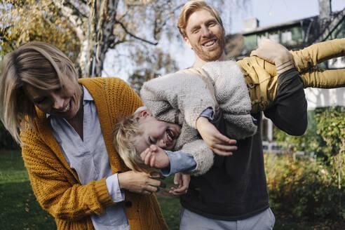 Happy family having fun in garden - KNSF07134