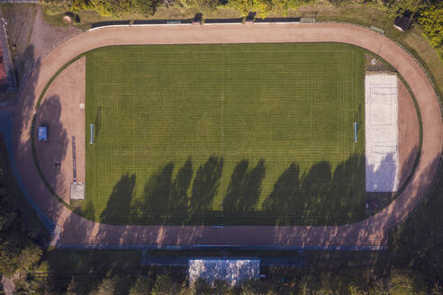 Germany, Baden-Wurttemberg, Freiburg im Breisgau, Aerial view of running track surrounding empty football field - DHEF00051