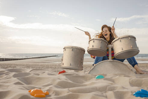 Portrait of laughing woman playing drums on the beach - KSHSF00021