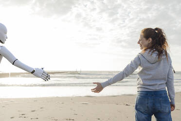 Smiling woman standing on the beach reaching for robot hand - KSHSF00027
