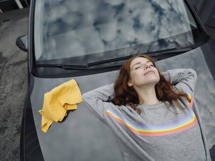 Redheaded woman lying on car bonnet - KNSF07146