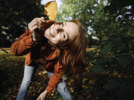 Portrait of happy redheaded woman holding autumn leaf - KNSF07152
