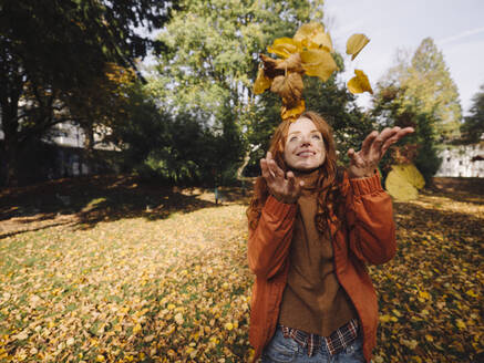 Happy redheaded woman enjoying autumn in a park - KNSF07158