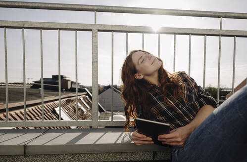 Redheaded woman with tablet relaxing on rooftop terrace - KNSF07161