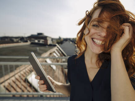 Portrait of happy redheaded woman with tablet on rooftop terrace - KNSF07170