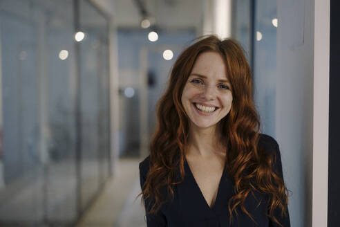 Portrait of happy redheaded woman on office floor - KNSF07179