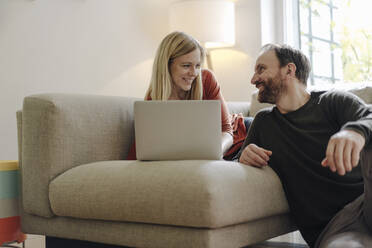 Couple sitting at home on couch, using laptop - KNSF07192