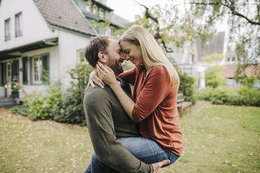Happy couple kissing in garden, in front of their dream house - KNSF07222