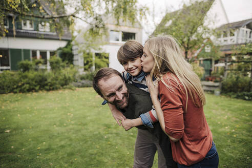 Parents and son having fun, playing in the garden - KNSF07240