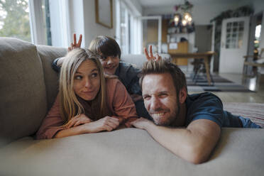 Happy family lying on couch, son making fun of his parents - KNSF07270