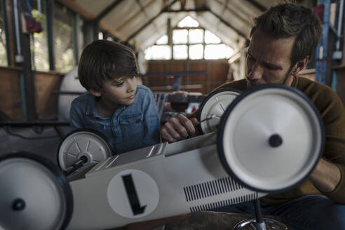 father and son repairing toy car in the barn - KNSF07276