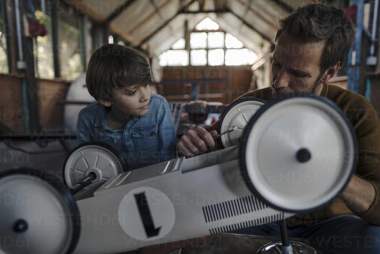father and son repairing toy car in the barn - KNSF07276 - Kniel Synnatzschke/Westend61