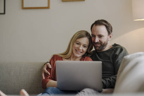 Couple sitting at home on couch, using laptop - KNSF07285