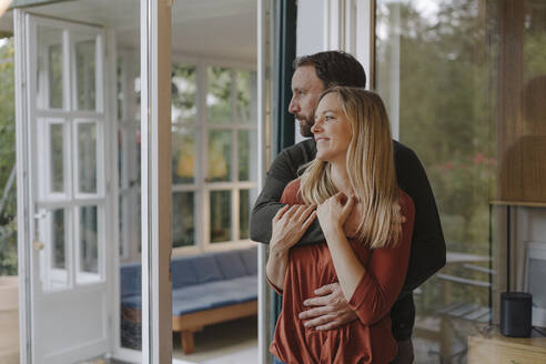 Happy couple embracing in their comfortable home - KNSF07306