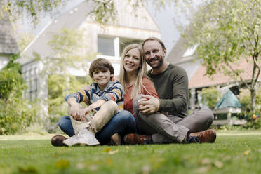 Happy family sitting on grass in their garden - KNSF07318
