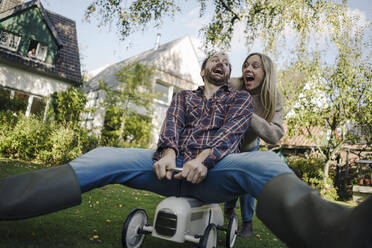 Laughing couple pretending to ride a toy car in the garden - KNSF07330