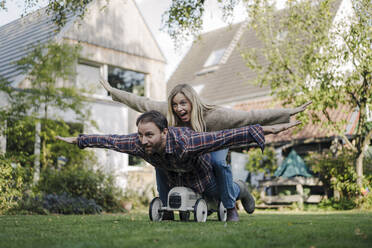 Laughing couple, pretending to fly on a toy car in the garden - KNSF07333