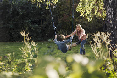 Son swinging in garden with his mother - KNSF07348