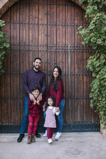 Portrait of smiling family with two children standing at wooden gate - GRCF00120
