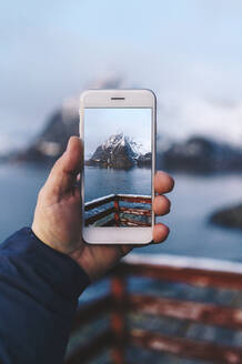 Close-up of tourist taking a smartphone picture at Hamnoy, Lofoten, Norway - DGOF00080
