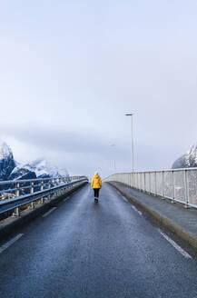 Tourist crossing a bridge at Hamnoy, Lofoten, Norway - DGOF00095